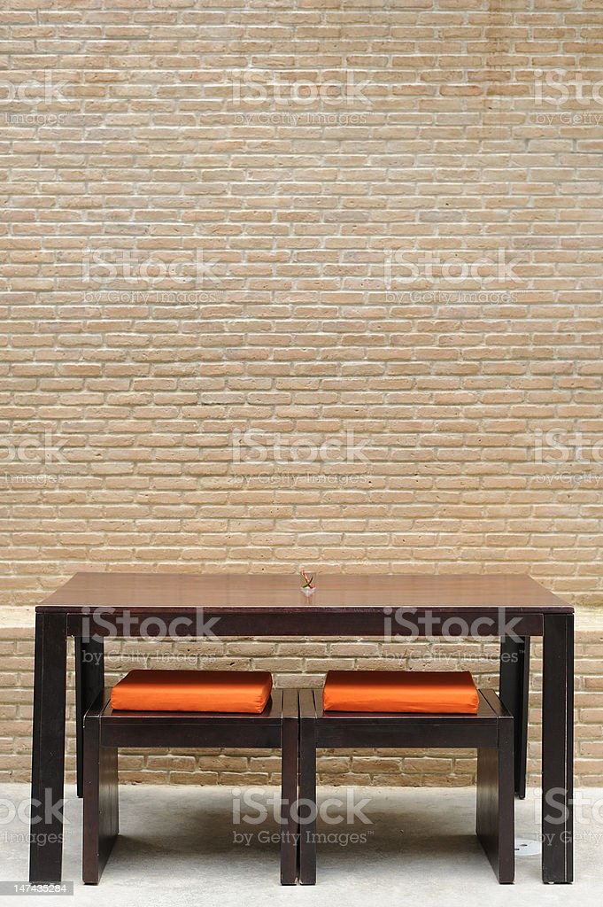 A brown dining table with two chairs on a brick wall royalty-free stock photo