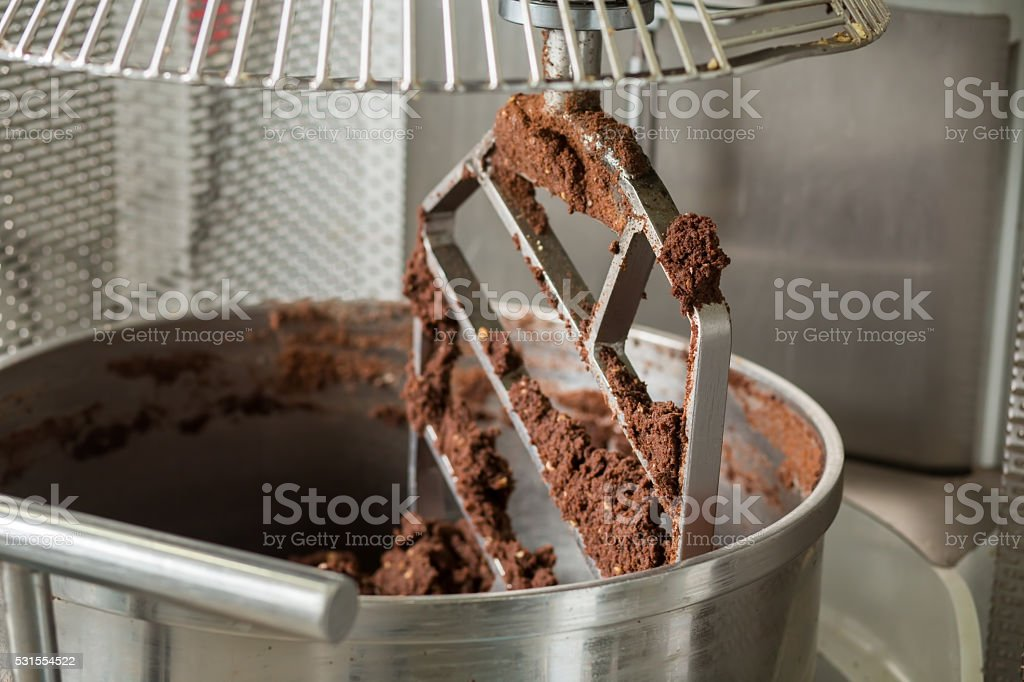 Brown dough inside industrial mixer. stock photo