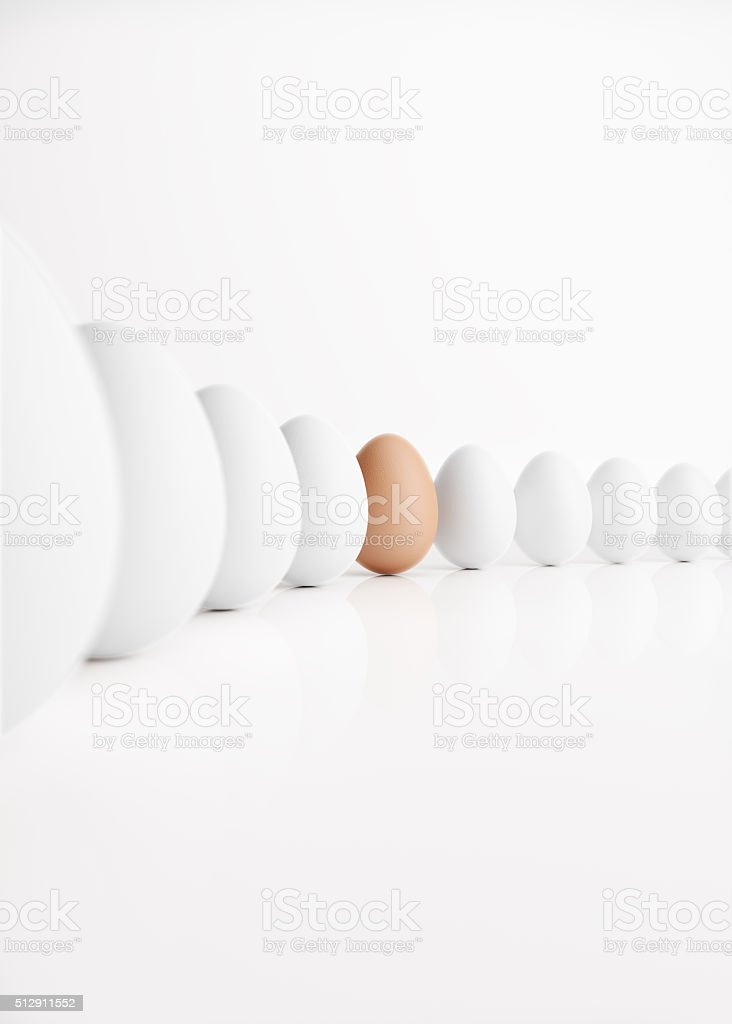 Brown Egg Standing Out from a Crowd of Ordinary Eggs stock photo