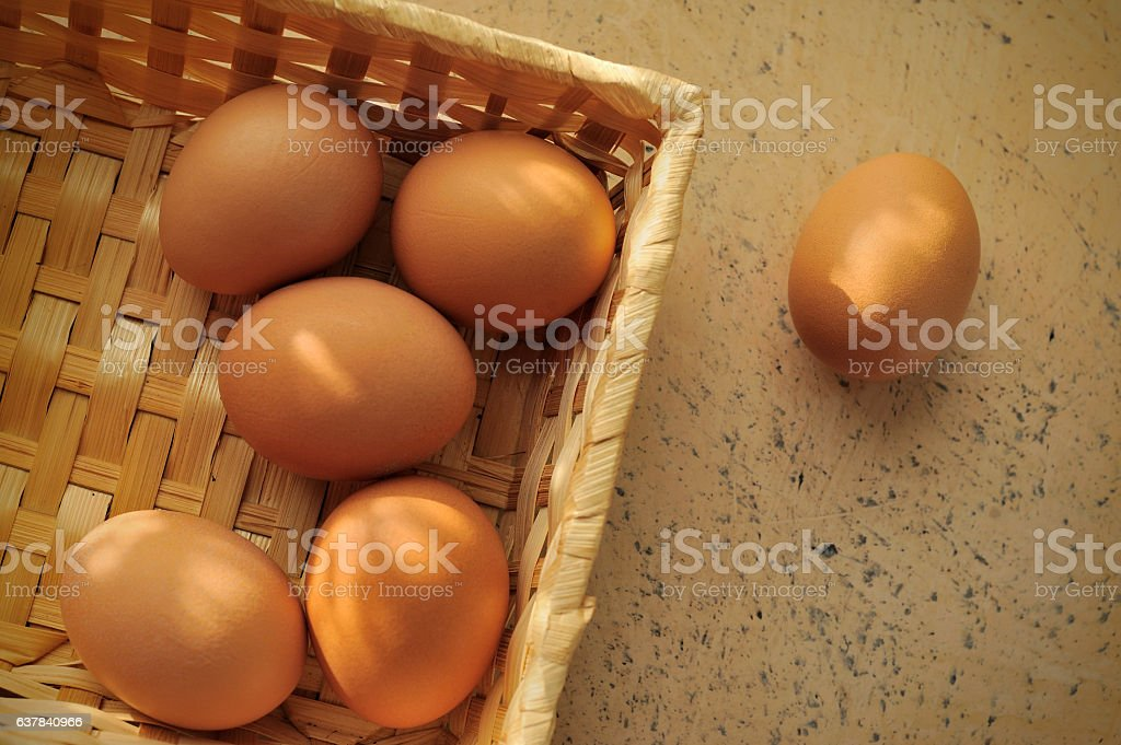 brown eggs in a basket on textured surface stock photo