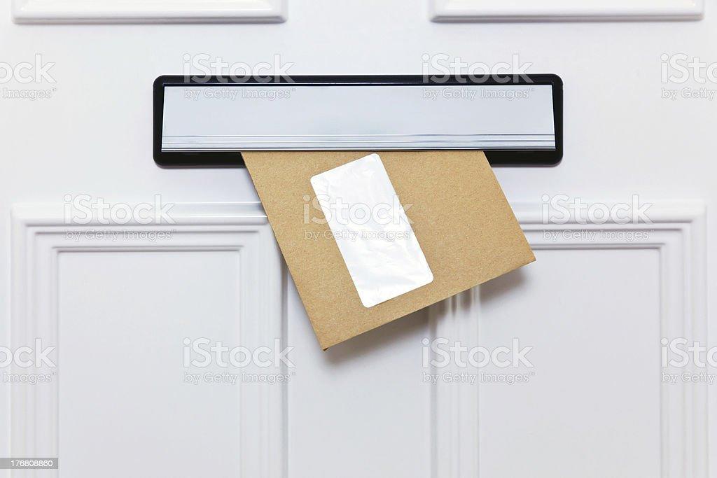Brown envelope in a front door letterbox stock photo