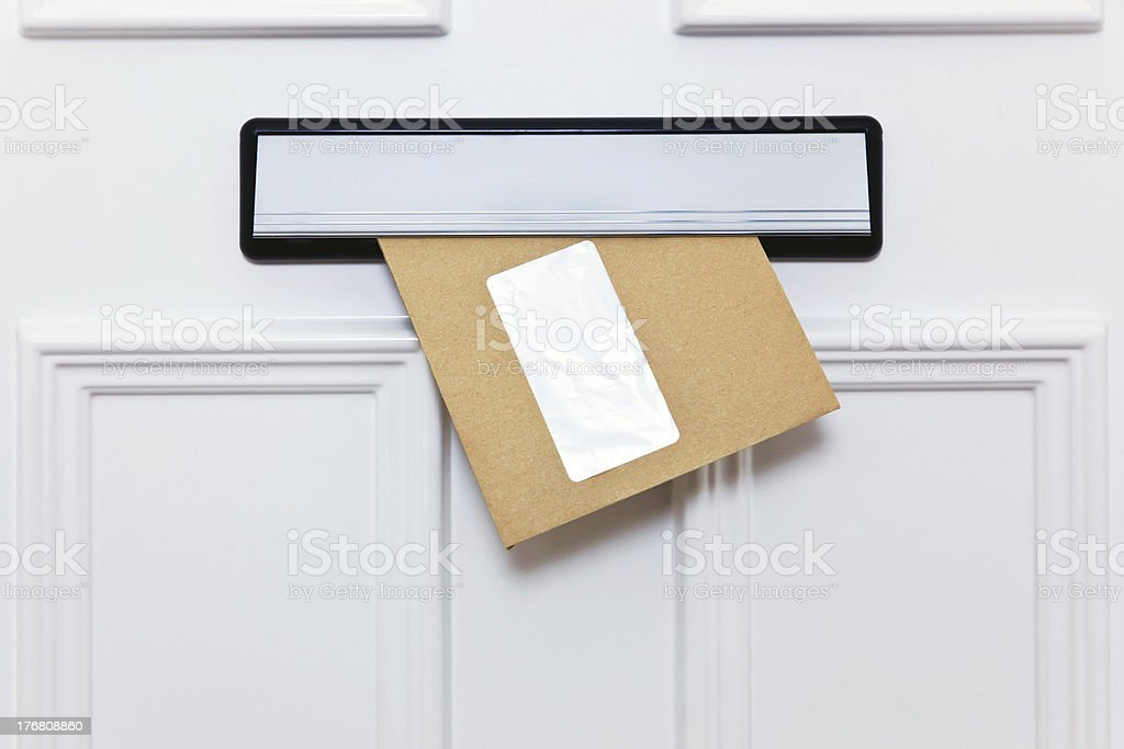 Brown envelope in a front door letterbox stock photo