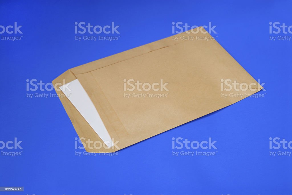 brown envelope laying flat on a blue background stock photo