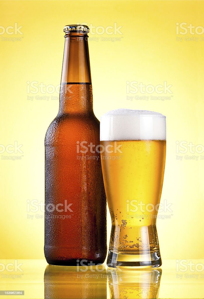 Brown full bottle covered with condensate and glass beer royalty-free stock photo