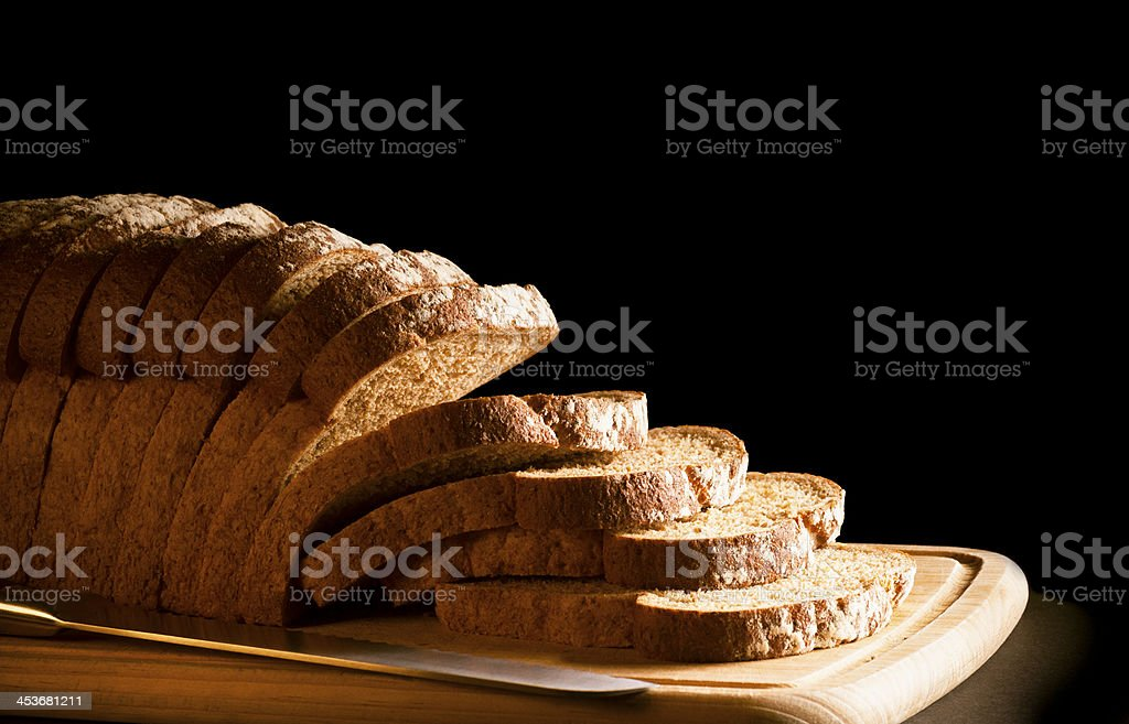 Brown granary wholemeal loaf sliced on wooden chopping board royalty-free stock photo