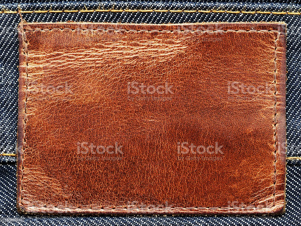 Brown grungy leather label on denim royalty-free stock photo