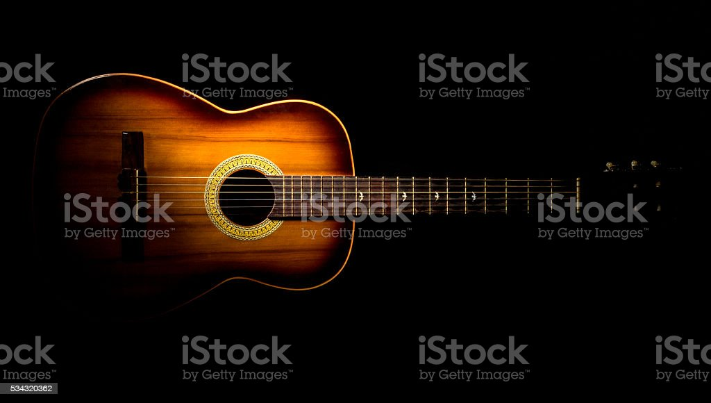 Brown guitar on a black background stock photo
