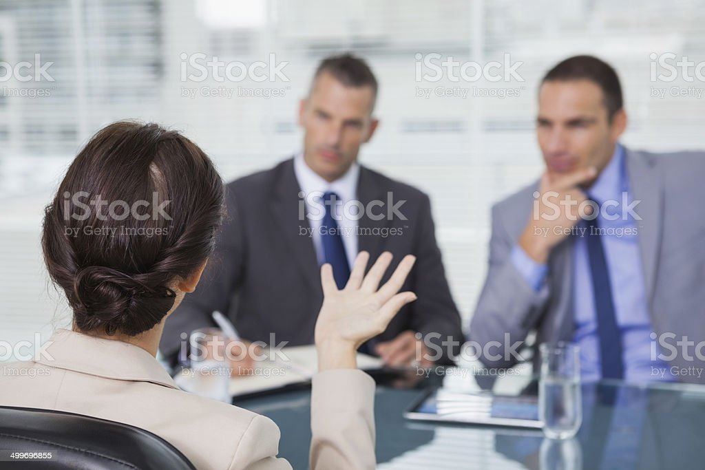 Brown haired woman talking to her interviewers stock photo