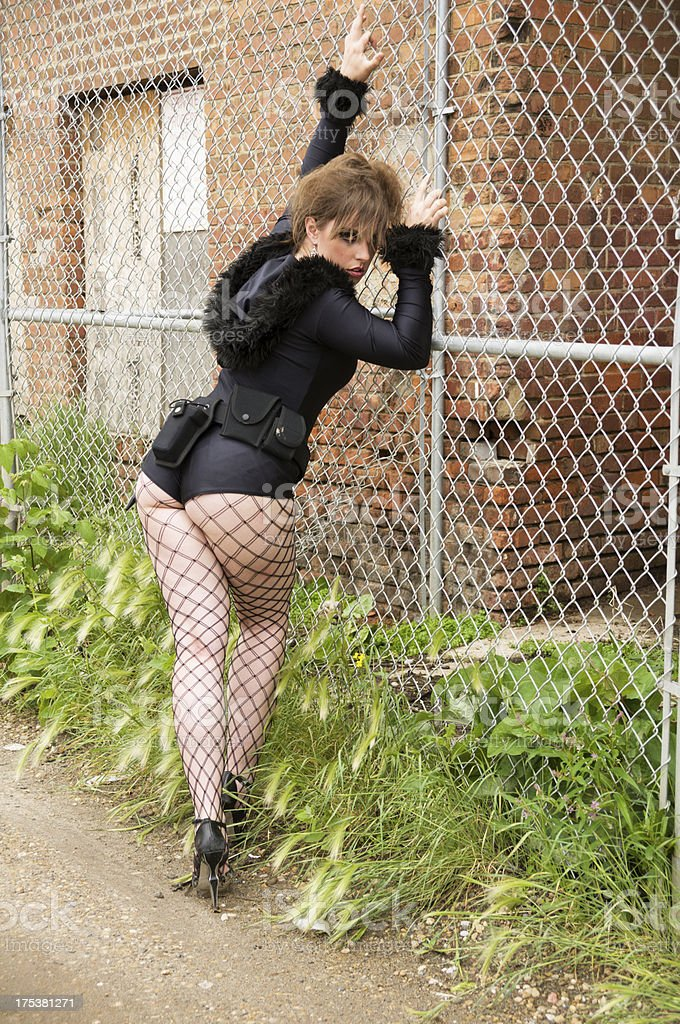 Brown haired young woman leaning on chainlink fence. stock photo