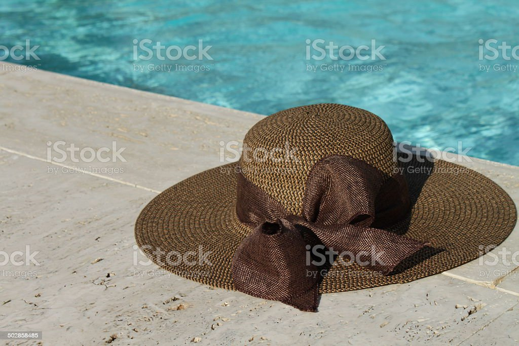 Brown hat on the swimming pool edge royalty-free stock photo
