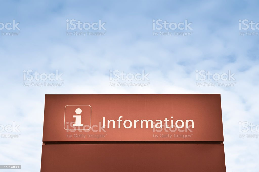 Brown information sign against a blue sky stock photo