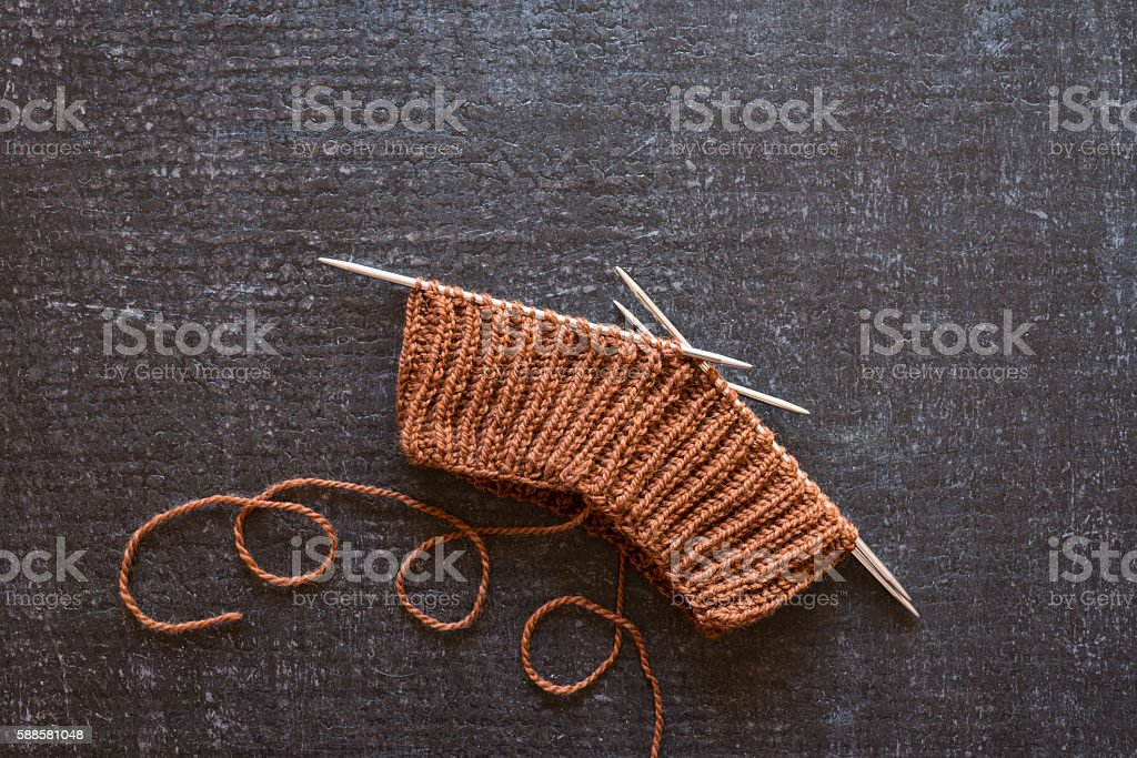 Brown knitting on black background stock photo