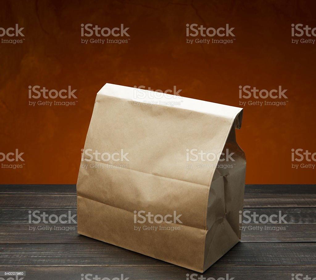 Brown kraft paper bag for lunch or food on wooden stock photo