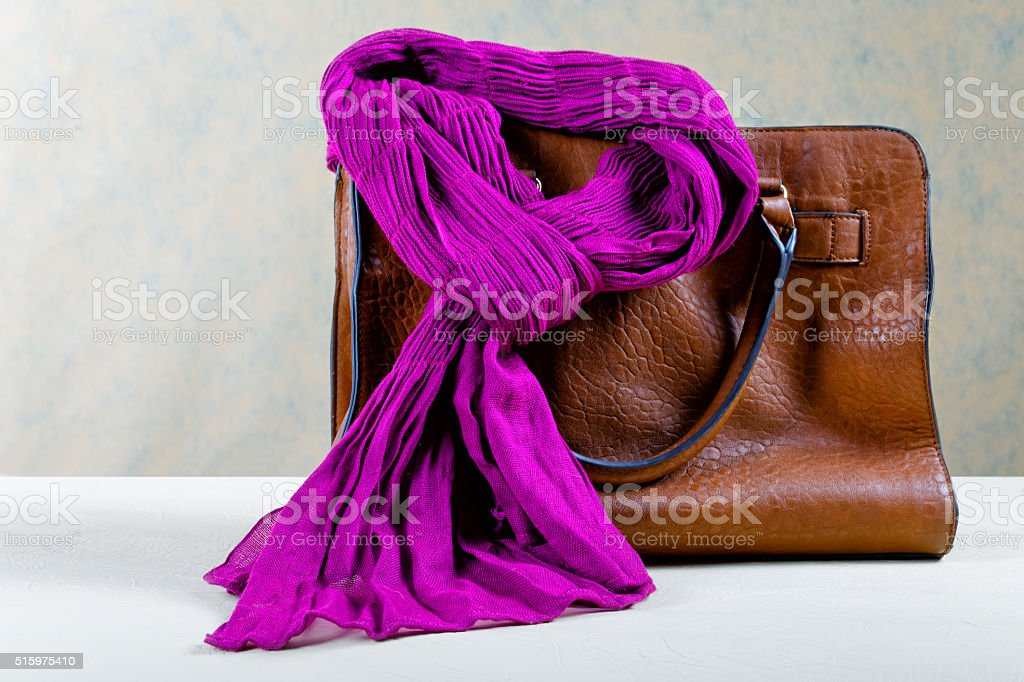 Brown leather bag and violet scarf stock photo