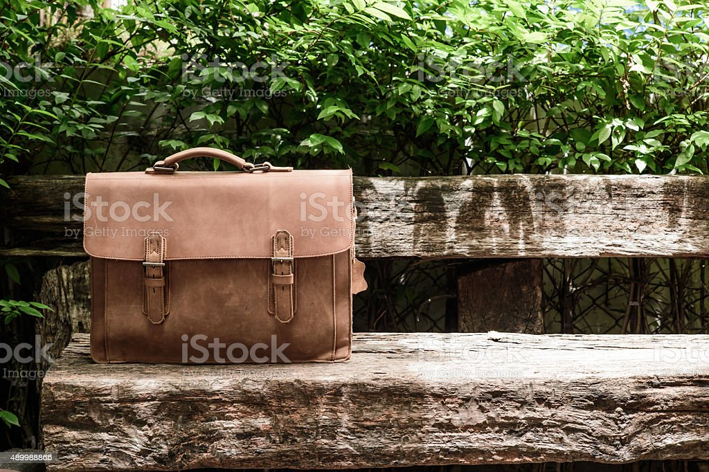 Brown Leather laptop bag corporate  on old wooden chair stock photo