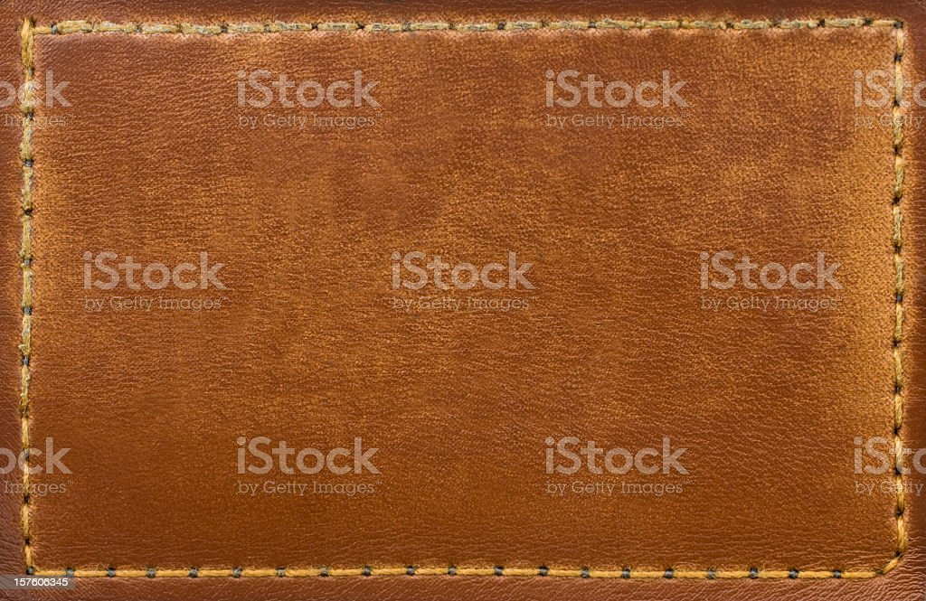 Brown leather patch with stitching along the edges stock photo