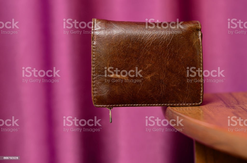 Brown leather wallet on edge of table stock photo