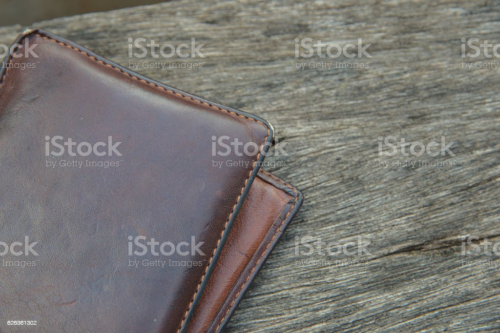 Brown leather wallet on wood background. stock photo