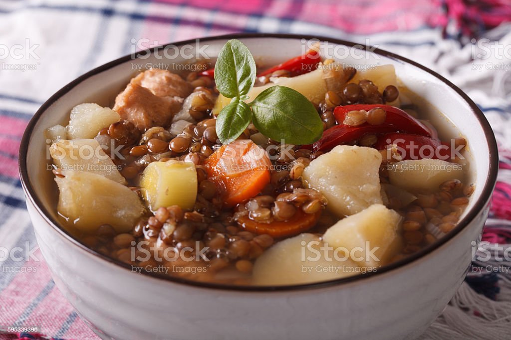 brown lentil soup with chicken and vegetables close-up. horizontal stock photo