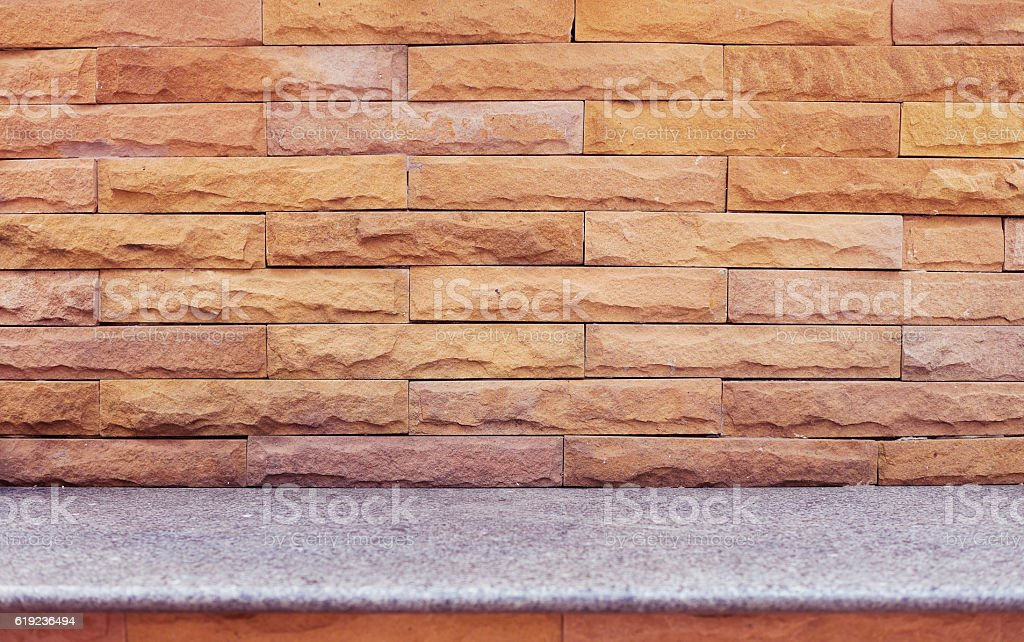 Brown marble brick wall with gray  marble seat stock photo