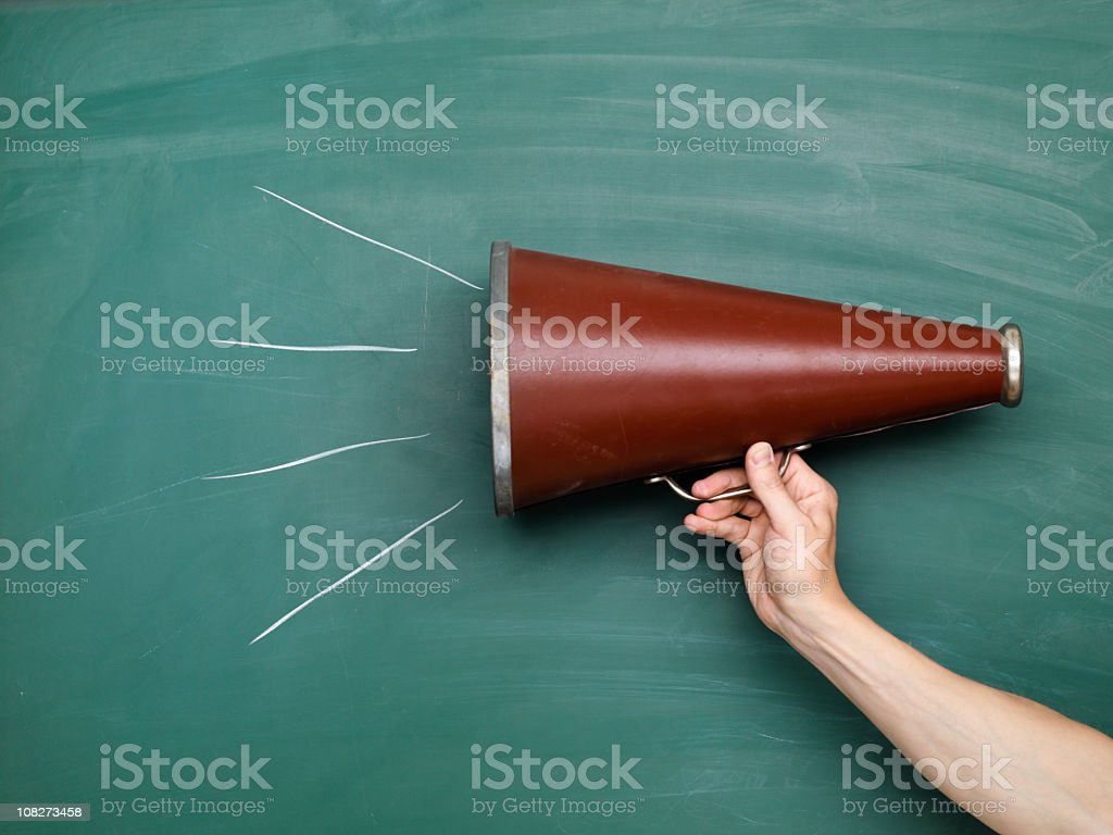 A brown megaphone in front of a green chalkboard with lines stock photo