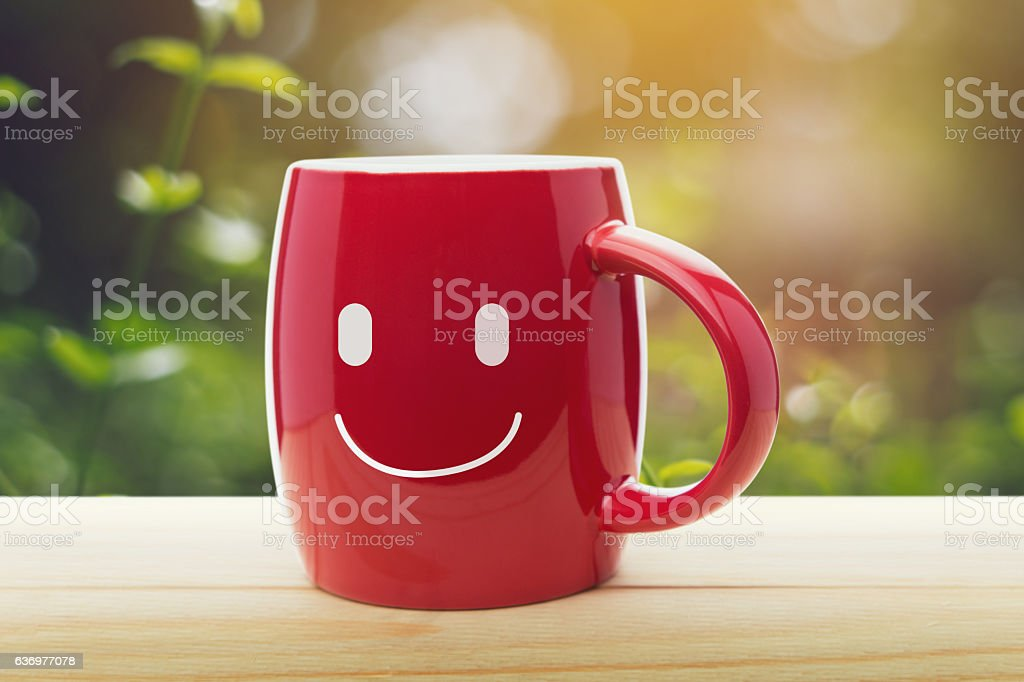 Brown mug of coffee with a happy smile stock photo