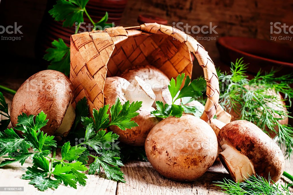 Brown mushrooms, parsley and dill, a wicker basket stock photo