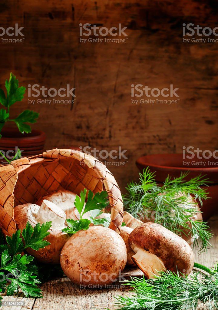 Brown mushrooms poured from wicker baskets stock photo