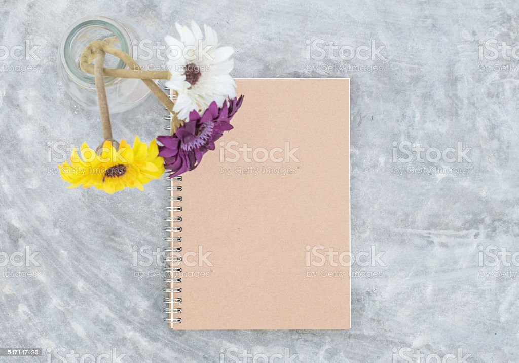 Brown note book with blurred artificial flower on glass bottle stock photo