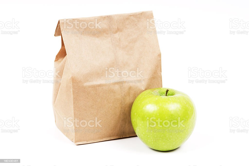 A brown paper bag containing lunch next to an apple royalty-free stock photo