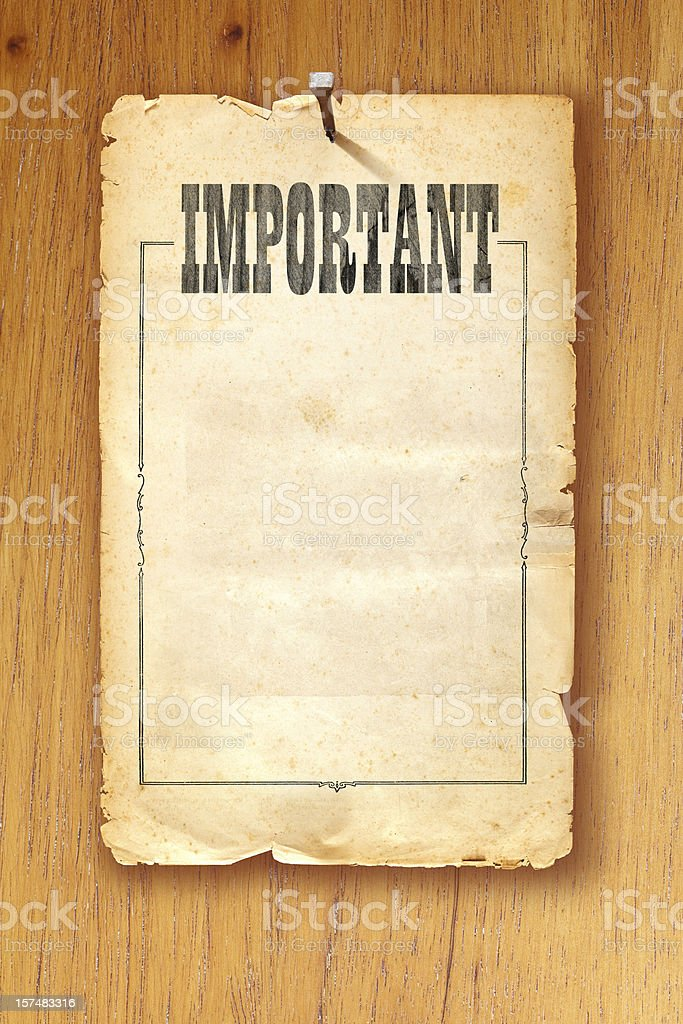 Brown paper fixed with nail on wooden background saying 'Important' royalty-free stock photo