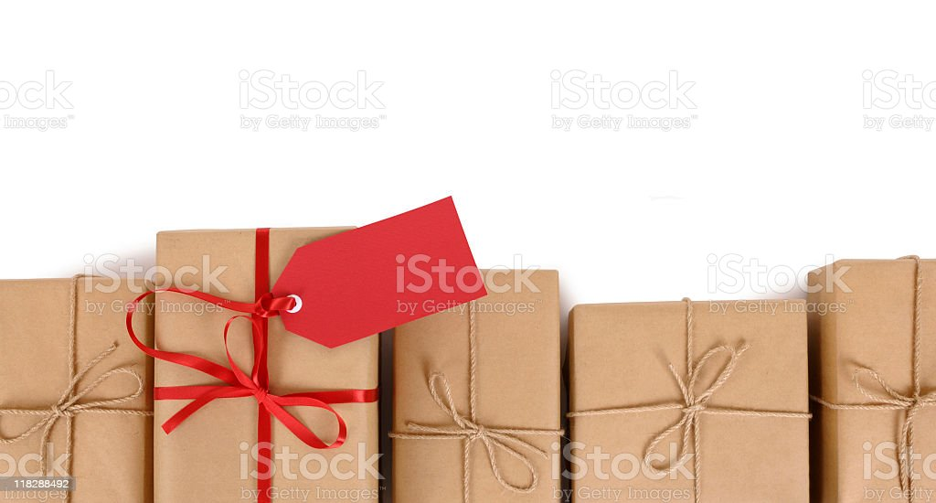 Brown paper package with red gift tag in row of plain ones stock photo