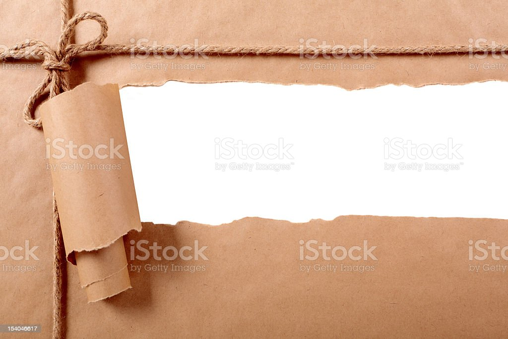 Brown paper package with torn section stock photo