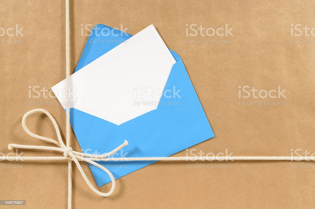 Brown paper parcel with blue envelope royalty-free stock photo