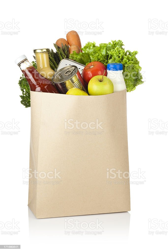 Brown paper shopping bag full of groceries on white backdrop stock photo
