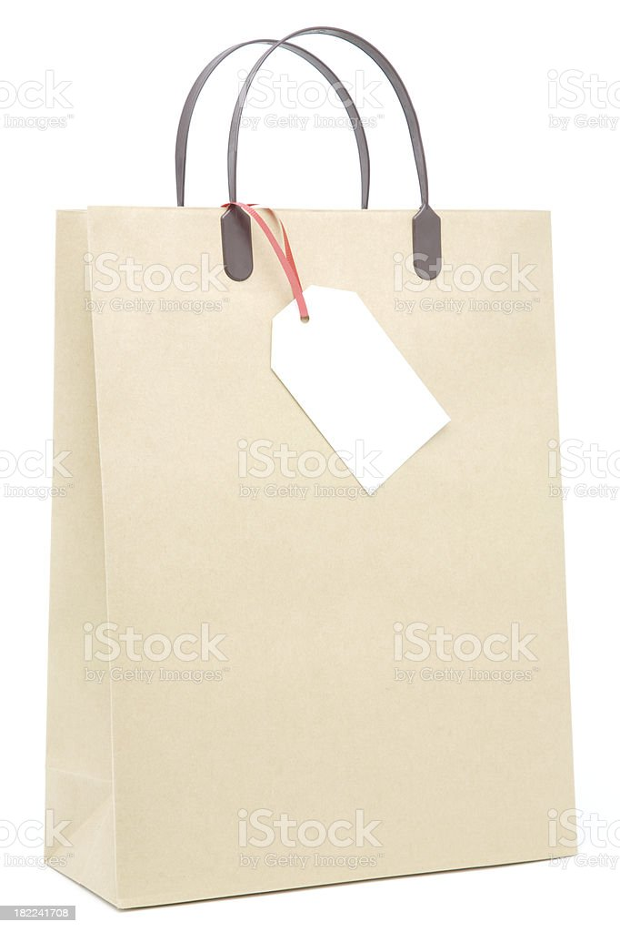 Brown paper shopping bag with blank label isolated royalty-free stock photo