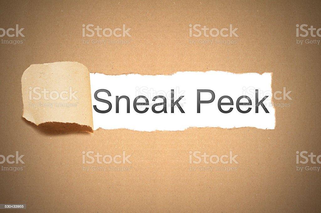 brown paper torn to reveal sneak peek stock photo