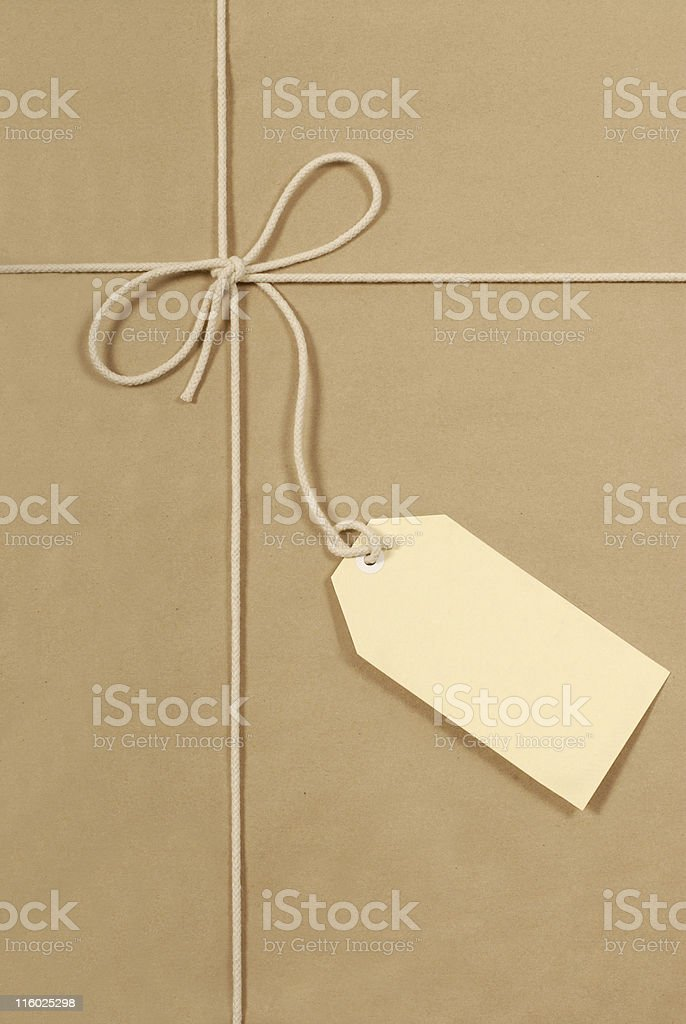 Brown parcel with cream cotton string and large label royalty-free stock photo