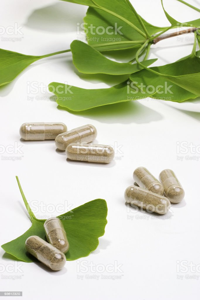 Brown pills laid down among green leaves royalty-free stock photo