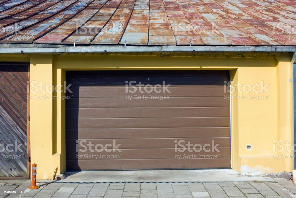 Brown plastic mass production automatic gate of city small-sized garage. Rusty tin roof and yellow wall. Sunny day stock photo