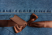 Brown ribbon on blue jeans texture