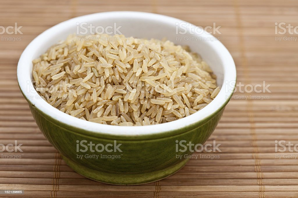 Brown rice in a green bowl stock photo