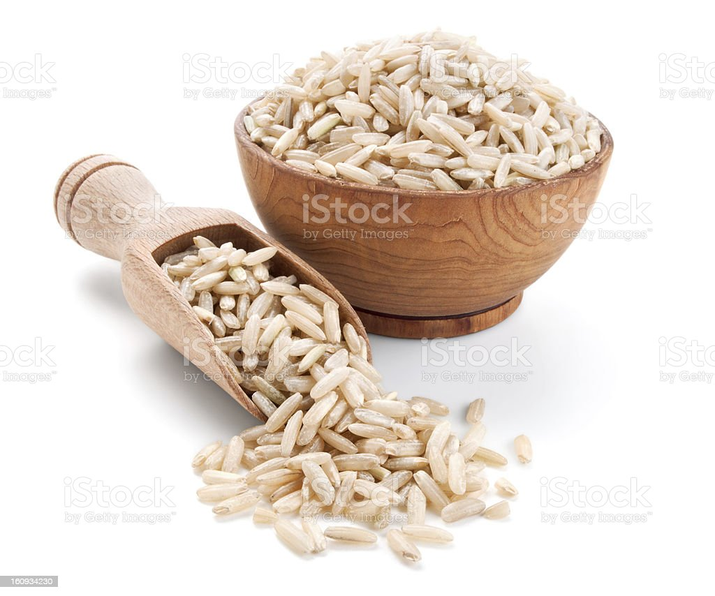 brown rice in a wooden bowl isolated on white stock photo