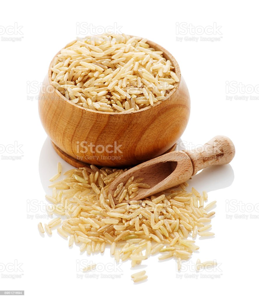 brown rice in a wooden bowl with a shove stock photo