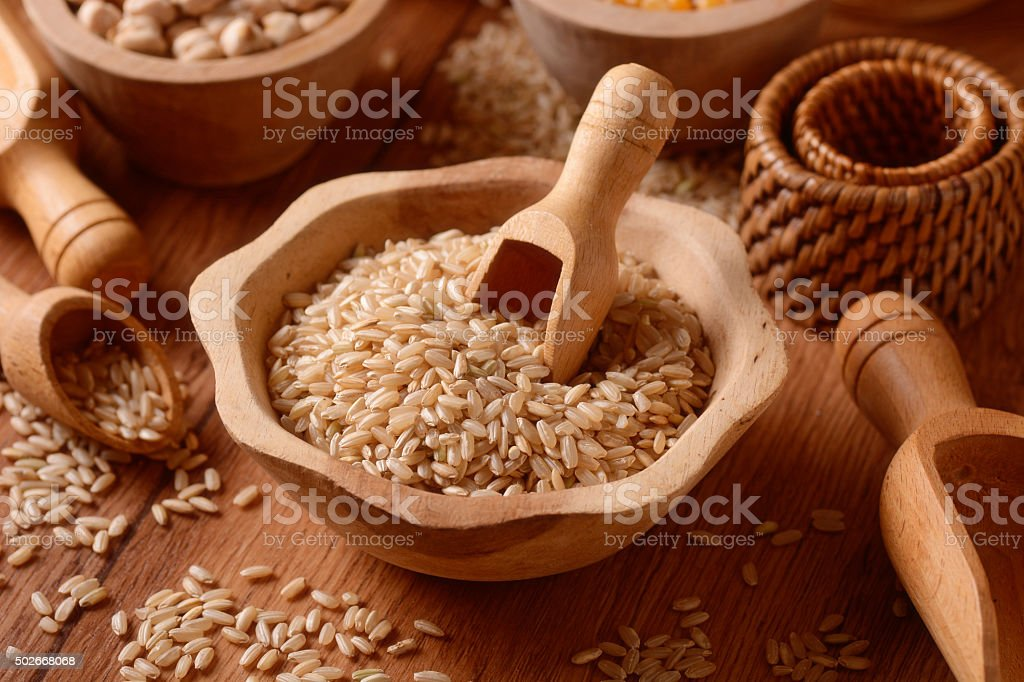 brown rice in foreground stock photo
