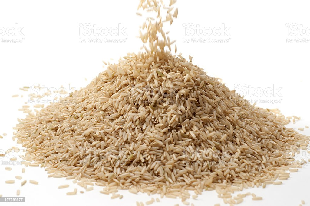 brown rice spilling onto pile royalty-free stock photo