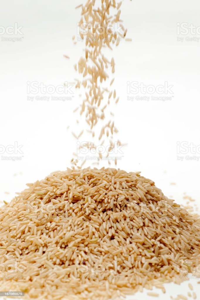 Brown rice spilling onto small pile royalty-free stock photo