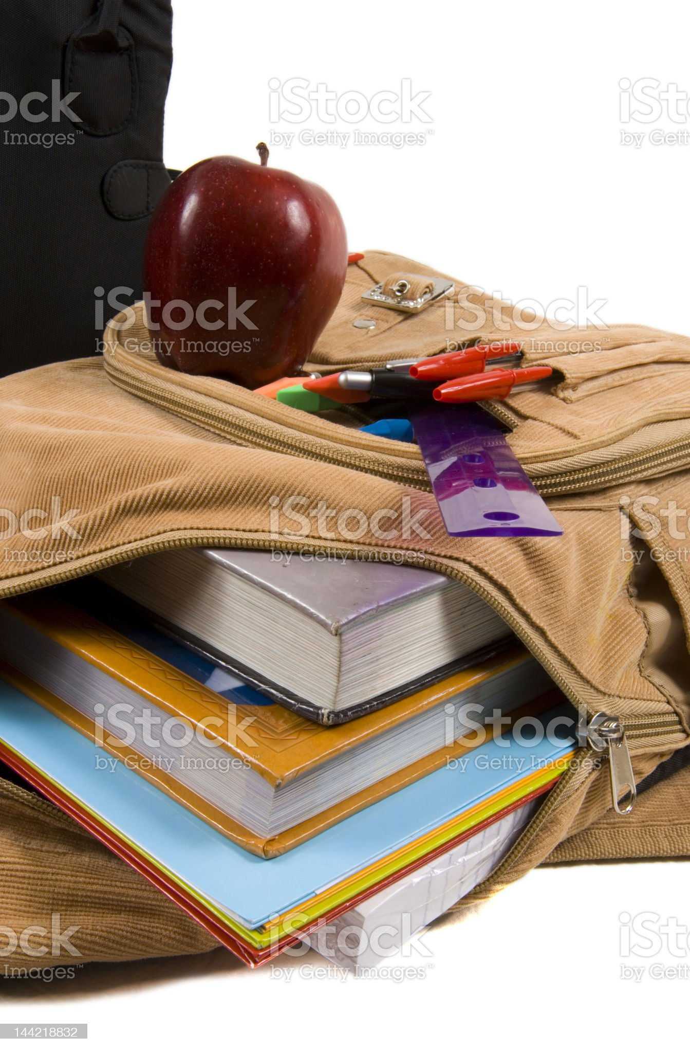 Brown School Back Pack full of supplies and an apple royalty-free stock photo