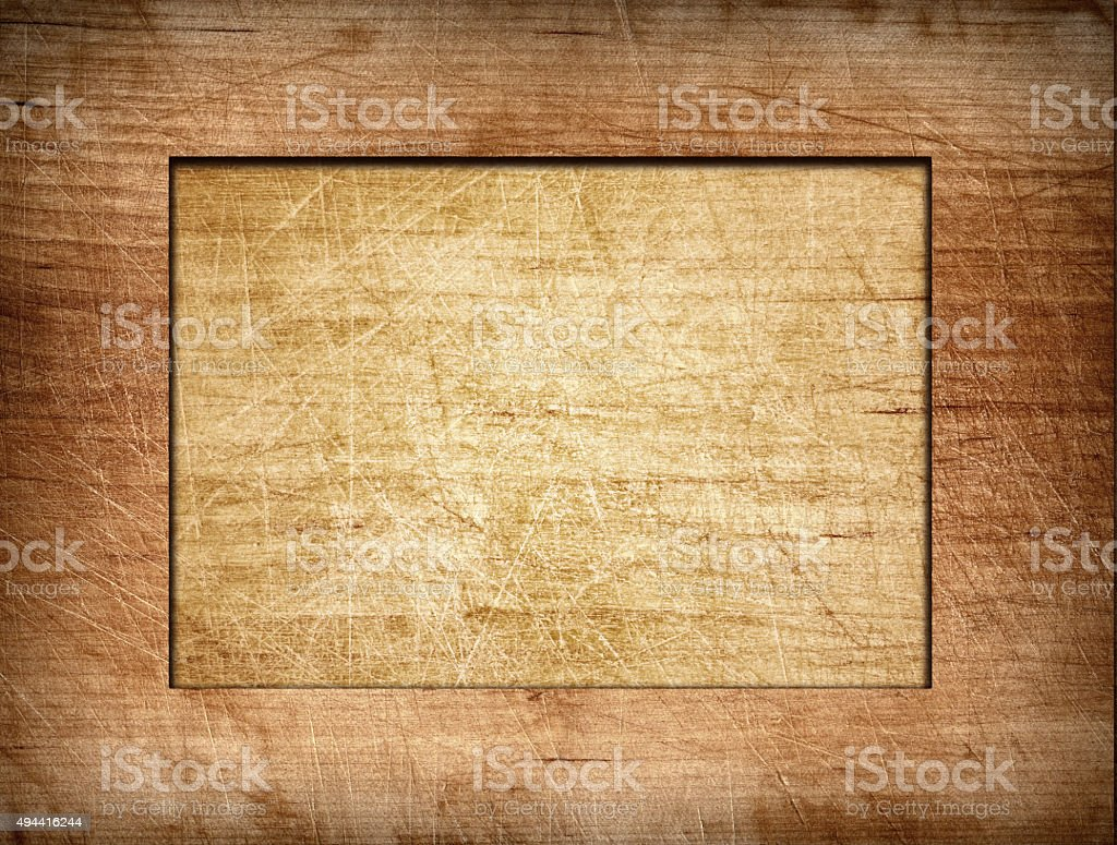 Brown scratched frame on light wooden board stock photo