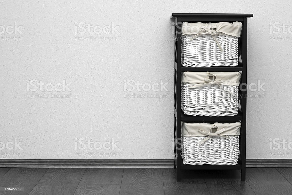 brown shelf with wicker baskets at white wall royalty-free stock photo